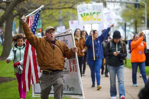 Joining thousands gathered outside the State Capitol, opponents of a bill to repeal Connecticut's religious exemption for required school vaccinations marches down Capitol Avenue before the State Senate voted on legislation, Tuesday, April 27, 2021, in Hartford, Conn.  A law adopted this week in Connecticut adds momentum to the push to strengthen vaccination requirements for schoolchildren, but efforts to give families more leeway are brewing in statehouses around the country in debates that go back more than a century.  (Mark Mirko/Hartford Courant via AP)