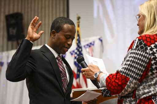 Mike Elliott takes the oath of office as the city's new mayor with city clerk Barb Suciu, right, during Elliot's inauguration ceremony, Wednesday, Jan. 2, 2019, at the Brooklyn Center Community Center, in Brooklyn Center, Minn. Elliott is the city's first Black and first Liberian American mayor. Elliott, who emigrated from Liberia as a child, is finding just how difficult it is to turn the page on the nation's racial history as he handles the fallout from a police shooting. (Aaron Lavinsky/Star Tribune via AP)