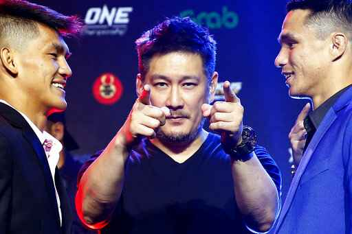 FILE - In this  July 30, 2019, file photo, One Championship founder Chatri Sityodtong, center, gestures as Reece McLaren, right, of Australia and Danny Kingad, of the Philippines face off during the media presentation for this ONE Championship mixed martial arts fight dubbed: Dawn of Heroes, in suburban Pasay city, south of Manila, Philippines. As his mixed martial arts promotions go behind closed doors and audience free, Sityodtong says he's finding ways to thrive during the coronavirus pandemic that is shutting down sports around the globe.  (AP Photo/Bullit Marquez, File)