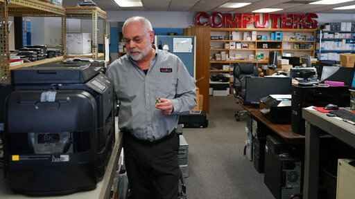 Independent repair shop owner Curtis Jones works on an Epson printer at The Technology Center in Sparks, Nev., Tuesday, March 30, 2021. Jones is among a group of independent repair shop owners who say tech companies have made it increasingly difficult to access parts and schematics needed to fix devices. He wants the state Legislature to pass a