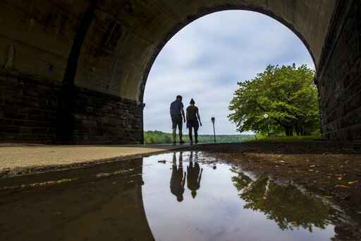 FILE - In this May 14, 2018 file photo, a couple walks on a path at Fairmount Park as they proceed under the trestle bridge over the Schuylkill River in Philadelphia. Tending your garden also offers lessons for growing your money. Start by defining what you want to bring to life. Think about the various aspects of your finances - income, expenses, debts - and imagine what you want them to look like in one or five years' time. (Michael Bryant/The Philadelphia Inquirer via AP)