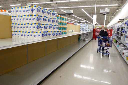 Shelves in the paper towel and toilet paper section are depleted at a Meijer Store in Carmel, Ind., Tuesday, Nov. 17, 2020. A surge of new coronavirus cases in the U.S. is sending people back to stores to stockpile again, leaving shelves bare and forcing retailers to put limits on purchases. (AP Photo/Michael Conroy)