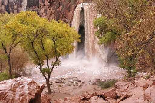 This Nov. 29, 2019, photo, shows a normally blue-green waterfall in Supai, Arizona, that turned chocolate brown after flooding. A popular tourist spot deep in a gorge off the Grand Canyon was flooded over the holiday, sending tourists scrambling to higher ground. The flood happened just days before the Havasupai Tribe shuts down its reservation to tourists for the season. No one was injured but some tourists woke up drenched and some lost camping gear. (Mandy Augustin via AP)
