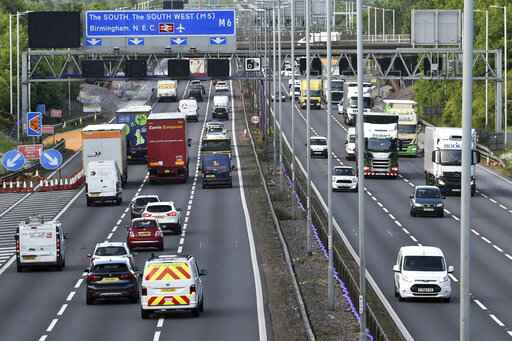 FILE - In this May 18, 2020, file photo, traffic moves along the M6 motorway near Birmingham, England. Britain will ban the sale of new gasoline and diesel cars by 2030, a decade earlier than its previous commitment, the prime minister said Tuesday, Nov. 17, 2020. Boris Johnson made the pledge as part of plans for a