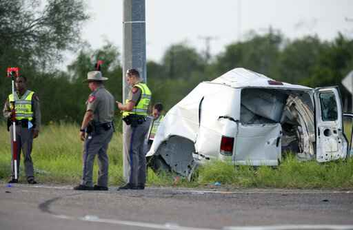 Texas Department of Public Safety officers stand near a vehicle where multiple people died after the van carrying migrants tipped over just south of the Brooks County community of Encino on Wednesday, Aug. 4, 2021, in Encino, Texas. The van crashed against a utility pole after it attempted to turn off of Highway 281 onto Business 281. Encino is about 2 miles (3.22 kilometers) south of the Falfurrias Border Patrol checkpoint. (Delcia Lopez/The Monitor via AP)
