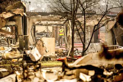 Utility worker Jake Orton examines a building destroyed by the Almeda Fire at the Parkview Townhomes in Talent, Ore., on Wednesday, Sept. 16, 2020. (AP Photo/Noah Berger)