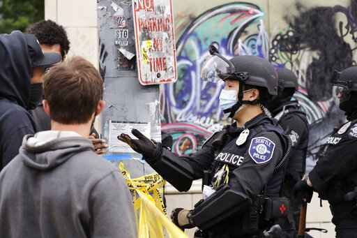 A police officer engages with a protester Wednesday, July 1, 2020, in Seattle, where streets had been blocked off in an area demonstrators had occupied for weeks. Seattle police showed up in force earlier in the day at the