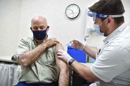 FILE - In this April 1, 2021 file photo Gov. Greg Gianforte receives a shot of the Pfizer COVID-19 vaccine from pharmacist Drew Garton at a Walgreen's pharmacy, in Helena, Mont. Gianforte has tested positive for COVID-19. The Republican governor's office released a statement Monday, April 5, 2021 evening saying that after experiencing mild symptoms a day earlier, Gianforte was tested