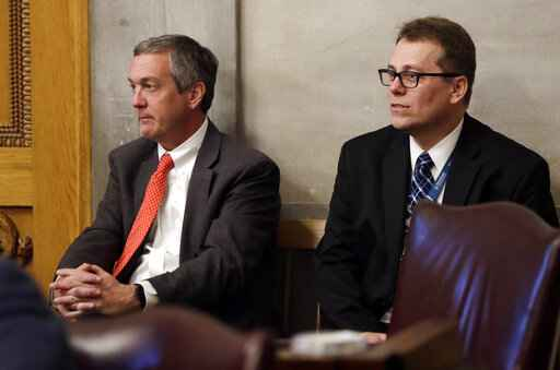 FILE - In this April 15, 2019, file photo, Tennessee Secretary of State Tre Hargett, left, attends a House session, in Nashville, Tenn. Hargett, who had previously argued the original 2019 voter registration law would bolster election security, is submitting a separate bill in 2020 that will criminalize