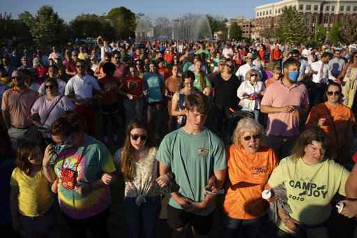 People participate in a memorial service and prayer vigil for the Lesslie family at Fountain Park, Sunday, April 11, 2021, in Rock Hill, S.C. Dr. Robert Lesslie and his wife, Barbara Lesslie, their grandchildren Adah Lesslie and Noah Lesslie, and two men working at the Lesslie home, Robert Shook and James Lewis, were fatally shot last week by former NFL player Phillip Adams. (AP Photo/Sean Rayford)