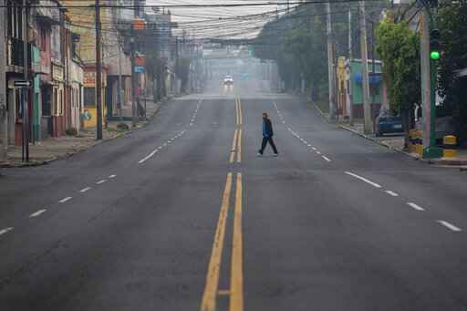 A woman crosses an street that's empty due to a tight lockdown in Guatemala City, early Friday, May 15, 2020. The government decreed a three-day, nationwide lockdown starting Friday to help contain the spread of the new coronavirus. (AP Photo/Moises Castillo)