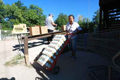 Barrios Unidos president Lupe Salazar pushes a dolly filled with canned food ahead of a food drive on Thursday, Sept. 23, 2021, in Chimayó, New Mexico. (AP Photo/Cedar Attanasio)