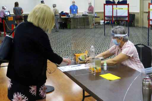 FILE - In this July 14, 2020, file photo, election worker Adonlie DeRoche, seated, wears a mask and face shield behind Plexiglas for safety during the coronavirus pandemic, while handing a ballot and single-use pen to a voter during the primary election in Portland, Maine. Thousands of U.S. election officials are busy sharing creative ideas they hope will keep voters and polling places safe from infection. (AP Photo/David Sharp, File)