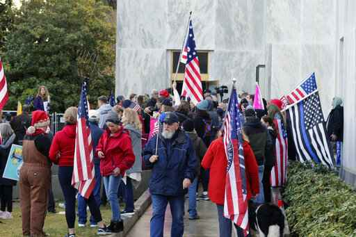FILE - In this Dec. 21, 2020, file photo, pro-Trump and anti-mask demonstrators hold a rally outside the Oregon State Capitol as legislators meet for an emergency session in Salem, Ore. During the protest Republican lawmaker, Rep. Mike Nearman, physically opened the Capitol's door - letting protesters, who clashed with police, gain access to the building. There have been calls for Nearman to resign ahead of the upcoming 2021 Legislative session that begins Tuesday, Jan. 19, 2021. (AP Photo/Andrew Selsky, File)