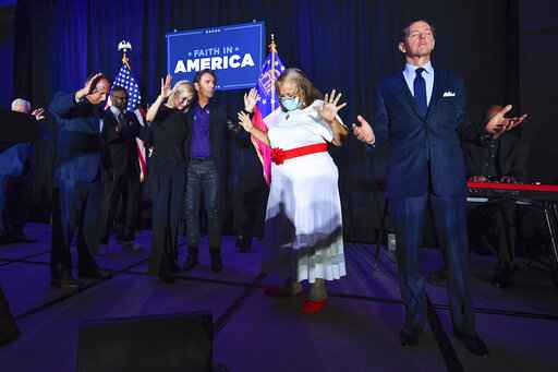 FILE - In this July 23, 2020, file photo, from right, Faith & Freedom Coalition founder Ralph Reed, Dr. Alveda King, Journey keyboardist Jonathan Cain, and White House faith adviser Paula White-Cain, and others pray on stage during an Evangelicals for Trump campaign event titled