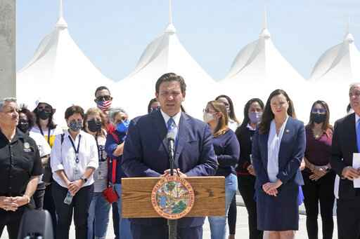 Florida Gov. Ron DeSantis, center, speaks during a news conference surrounded by officials and cruise workers, Thursday, April 8, 2021, at PortMiami in Miami. DeSantis announced a lawsuit against the federal government and the CDC demanding that cruise ships be allowed to sail. (AP Photo/Wilfredo Lee)