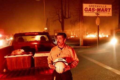 Battalion Chief Sergio Mora watches as the Dixie Fire tears through the Greenville community of Plumas County, Calif., on Wednesday, Aug. 4, 2021. The fire leveled multiple historic buildings and dozens of homes in central Greenville. (AP Photo/Noah Berger)