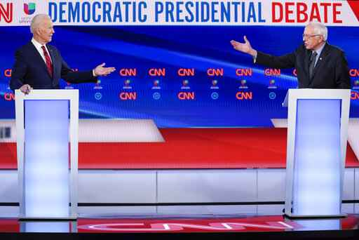 FILE - In this March 15, 2020, file photo former Vice President Joe Biden, left, and Sen. Bernie Sanders, I-Vt., right, participate in a Democratic presidential primary debate at CNN Studios in Washington. U.S. elections have been upended by the coronavirus pandemic. At least 13 states have postponed voting and more delays are possible as health officials warn that social distancing and other measures to contain the virus might be in place for weeks, if not months. (AP Photo/Evan Vucci, File)