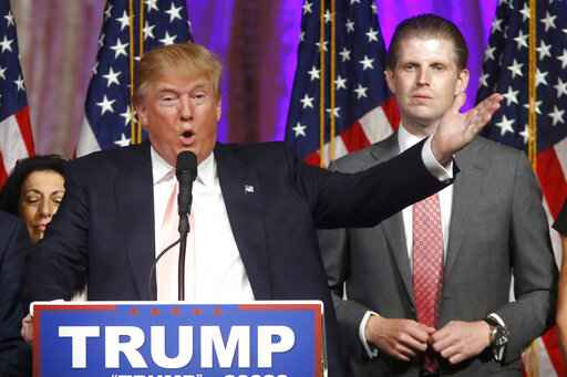 FILE - In this Tuesday, March 15, 2016, file photo, Republican presidential candidate Donald Trump speaks to supporters at his primary election night event at his Mar-a-Lago Club in Palm Beach, Fla. At right is his son Eric Trump. Hits to President Donald Trump's business empire since the deadly riots at the U.S. Capitol are part of a liberal