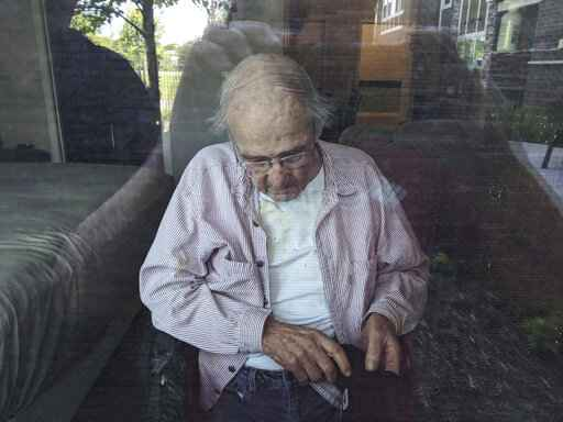 This June 7, 2020, photo provided by June Linnertz shows her father, James Gill, seen through a window at Cherrywood Pointe nursing home in Plymouth, Minn. As more than 90,000 of America's long-term care residents have died in the coronavirus pandemic, advocates for the elderly say a tandem wave of death separate from the virus has quietly claimed tens of thousands more, often because overburdened workers haven't been able to give them the care they need. Gill died of Lewy Body Dementia, according to a copy of his death certificate provided to the AP. Linnertz always expected her father to die of the condition, which causes a progressive loss of memory and movement, but never thought he would end his days in so much needless pain. (June Linnertz via AP)