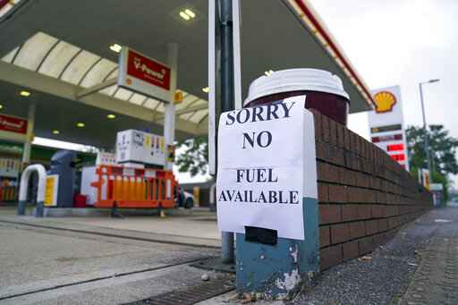 A view of a sign at a petrol station, in Bracknell England, Sunday Sept. 26, 2021. In a U-turn, Britain says it will issue thousands of emergency visas to foreign truck drivers to help fix supply-chain problems that have caused empty supermarket shelves, long lines at gas stations and shuttered petrol pumps. (Steve Parsons/PA via AP)