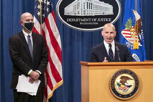 Steven D'Antuono, head of the Federal Bureau of Investigation (FBI) Washington field office, left, listens as acting U.S. Attorney Michael Sherwin, speaks during a news conference Tuesday, Jan. 12, 2021, in Washington. Federal prosecutors are looking at bringing