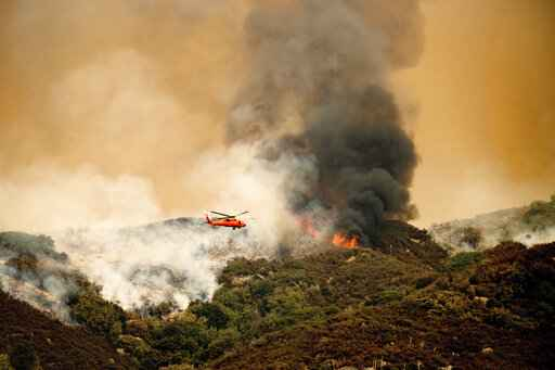 A helicopter prepares to drop water on the KNP Complex Fire in Sequoia National Park, Calif., on Wednesday, Sept. 15, 2021. The blaze is burning near the Giant Forest, home to more than 2,000 giant sequoias. (AP Photo/Noah Berger)