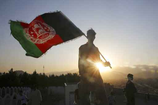 FILE - In this Aug. 19, 2019, file photo, a man waves an Afghan national flag during Independence Day celebrations in Kabul, Afghanistan. Washington's watchdog warns, Thursday, June 25, 2020,  that