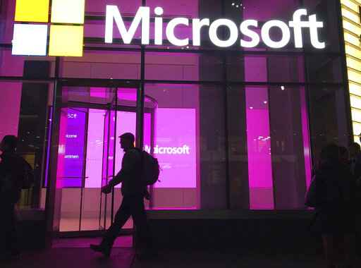FILE - In this Nov. 10, 2016, file photo, people walk near a Microsoft office in New York. Microsoft, on an accelerated growth push, is buying speech recognition company Nuance in a deal worth $19.7 billion including debt.  (AP Photo/Swayne B. Hall, File)