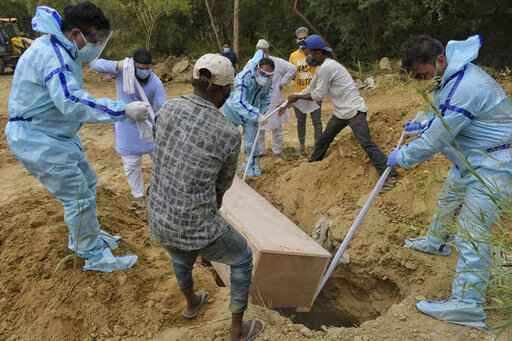 Relatives bury the body of a COVID-19 victim at a graveyard in New Delhi, India, Tuesday, May 4, 2021. India's official count of coronavirus cases surpassed 20 million Tuesday, nearly doubling in the past three months, while deaths officially have passed 220,000. Staggering as those numbers are, the true figures are believed to be far higher, the undercount an apparent reflection of the troubles in the health care system. (AP Photo/Ishant Chauhan)