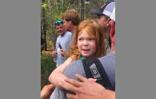 In a photo provided by Clay Carson, rescuers carry 4-year-old Vadie Sides out of the woods in Lee County, Ala., Friday, March 27, 2020. Lee County Sheriff Jay Jones said the girl was found with a dog at her side after two days in the woods. Authorities said the girl wandered away from a sitter while in a backyard. (Clay Carson via AP)