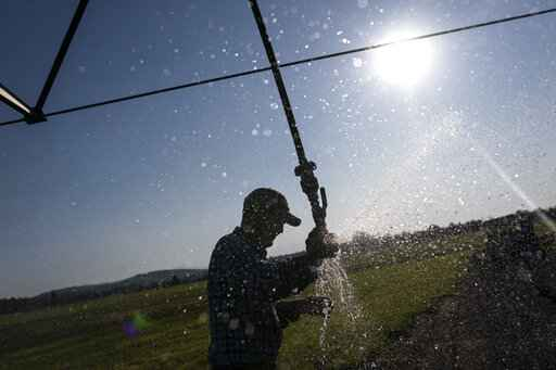 Matt Lisignoli shuts off an irrigation sprinkler at his farm, Smith Rock Ranch, in the Central Oregon Irrigation District on Tuesday, Aug. 31, 2021, in Terrebonne, Ore. The stark contrast between the water haves and have-nots two hours southeast of Portland has brought new urgency to efforts to share the resource. Proposals to create