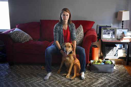Melissa Wilhelm Szymanski sits with her dog Cooper at home in Glastonbury, Conn., on Saturday, Sept. 19, 2020. Wilhelm Szymanski got sick earlier this year and wound up with a $3,200 bill because she wasn't diagnosed initially with COVID-19. Even though dozens of insurers and the federal government are offering to pick up all treatment costs during the pandemic, many holes remain for big bills to surprise patients. (AP Photo/Jessica Hill)