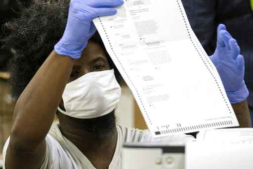 FILE - In this Nov. 25, 2020 file photo, workers scan ballots as the Fulton County presidential recount gets under way  at the Georgia World Congress Center in Atlanta. Reports from an independent monitor who observed election operations in Georgia's most populous county during the 2020 election cycle detail tense encounters with party election monitors.   (AP Photo/Ben Gray)