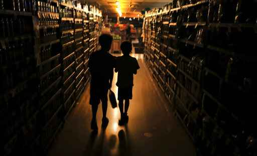 FILE - In this Oct. 23, 2019, file photo, Elijah Carter 11, left, and Robert Haralson, 12, help shop for their parents in a darkened Olivers Supermarket during a blackout in the Rincon Valley community in Santa Rosa, Calif. When Pacific Gas & Electric set up emergency operations centers to coordinate intentional blackouts intended to prevent wildfires in Northern California, the nation's largest utility forgot one thing, emergency managers who knew the fundamentals of emergency management in California. (Kent Porter/The Press Democrat via AP, File)
