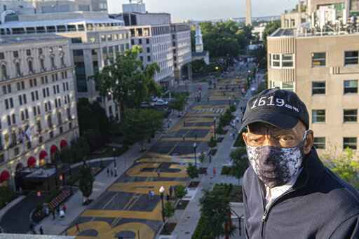 In this June 7, 2020 photo provided by the Executive Office of District of Columbia Mayor Muriel Bowser, John Lewis looks over a section of 16th Street that's been renamed Black Lives Matter Plaza in Washington.  The Washington Monument and the White House are visible in the distance.  Lewis, a lion of the civil rights movement whose bloody beating by Alabama state troopers in 1965 helped galvanize opposition to racial segregation, and who went on to a long and celebrated career in Congress, died. He was 80.  (Khalid Naji-Allah/Executive Office of the Mayor via AP)