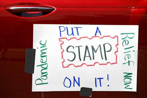 Part of a car caravan of postal employees has a sign on it asking Congress to approve emergency funding for the Postal Service, Tuesday, June 23, 2020, on Capitol Hill in Washington. The U.S. Postal Service's famous motto -
