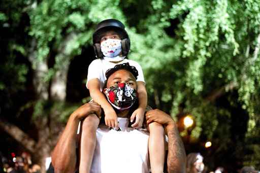 Leshan Terry hold his son Leshan Terry, Jr., 6, during a Black Lives Matter protest at the Mark O. Hatfield United States Courthouse on Friday, July 31, 2020, in Portland, Ore. Following an agreement between Democratic Gov. Kate Brown and the Trump administration to reduce federal officers in the city, nightly protests remained largely peaceful without major confrontations between demonstrators and officers. (AP Photo/Noah Berger)