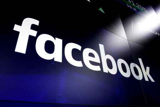 FILE - This March 29, 2018, file photo shows the Facebook logo on screens at the Nasdaq MarketSite, in New York's Times Square. A civil rights group is suing Facebook and its executives, saying CEO Mark Zuckerberg made