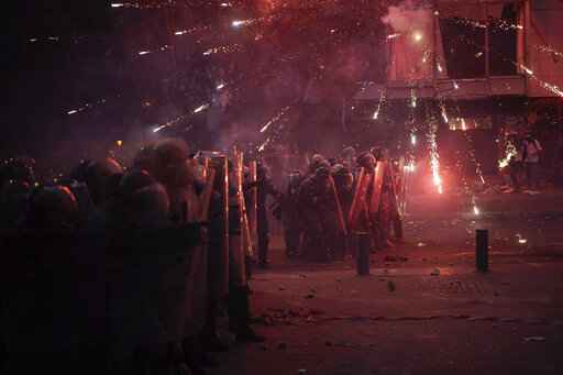 Fireworks thrown by anti-government protesters explode over Riot Police during clashes near the parliament building following last Tuesday's massive explosion in the seaport which devastated Beirut, Lebanon, Monday, Aug. 10, 2020. (AP Photo/Felipe Dana)