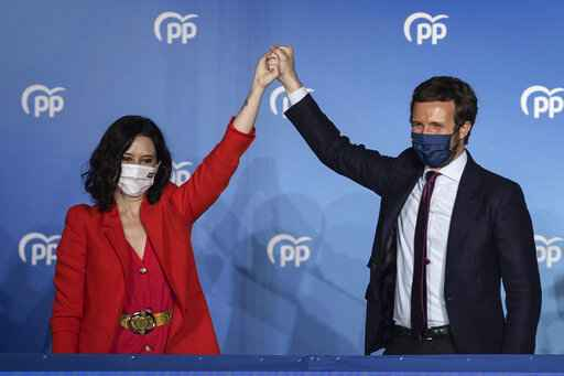 Conservative Madrid regional president Isabel Diaz Ayuso, left, and Popular party leader Pablo Casasdo wave outside the popular party headquarters in Madrid, Spain, Tuesday, May 4, 2021. Madrid residents voted in droves for a new regional assembly in an election that tests the depths of resistance to virus lockdown measures and the divide between left-wing and right-wing parties. Regional President Isabel Díaz Ayuso, who called the early election by dissolving her center-right coalition, had set off to broaden her power base and open up to an alliance with the far-right. (AP Photo/Bernat Armangue)