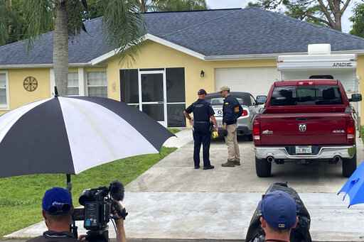 Law enforcement officials investigate home of a young man wanted for questioning in the disappearance of his girlfriend, Gabby Petito, on Monday, Sept. 20, 2021 in North Port, Fla.  The officers served a search warrant at the home of the parents of her 23-year-old boyfriend Brian Laundrie, who is wanted for questioning. (AP Photo/Curt Anderson)