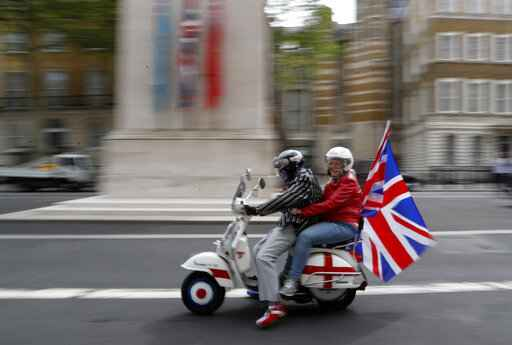 People on a Vespa adorned with a Union Flag ride past the Centotaph in Whitehall in London, Friday, May 8, 2020 on the 75th anniversary of the end of World War II in Europe. The 75th anniversary of the end of World War II in Europe should be all about parades, remembrances, and one last great hurrah for veteran soldiers who are mostly in their nineties. Instead, it is a time of coronavirus lockdown and loneliness spent in search of memories both bitter and sweet. (AP Photo/Frank Augstein)