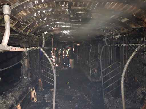 In this Friday, March 27, 2020, photo provided by the Fire Department of the City of New York, authorities examine the remains of a subway car after it was destroyed by fire. Officials said a fire in a shopping cart on the subway train led to the death of the train's operator and injuries to several other people early Friday. The incident is being investigated as a crime. (FDNY via AP)
