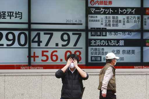 People walk by an electronic stock board of a securities firm in Tokyo, Wednesday, April 28, 2021. Asian shares are mostly higher as investors await a meeting of the Federal Reserve and a speech to Congress by U.S. President Joe Biden. (AP Photo/Koji Sasahara)