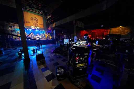 In this Oct. 26, 2020, photo, production engineers record the band Galactic for a video stream concert, inside an empty Tipitina's music club, which the band owns, in New Orleans. Music clubs all over the nation - pop culture icons like the Troubadour in West Hollywood, the Bluebird Cafe in Nashville, The Bitter End in New York's Greenwich Village - are shuttered due to the coronavirus. And owners fear for the future of their businesses and of a musical way of life. (AP Photo/Gerald Herbert)