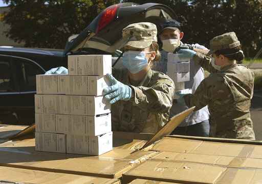 FILE - In this Wednesday, May 27, 2020, file photo, Oregon National Guard's Ashley Smallwood, of Springfield, Ore., counts out boxes of face masks to be given to Willamette Valley farmers while participating in a distribution event at the Oregon State University Extension Service-Linn County office in Tangent, Ore. Oregon adopted a controversial rule on Tuesday, May 4, 2021 that indefinitely extends coronavirus mask and social distancing requirements in all businesses in the state. State officials say the rule, which garnered thousands of public comments, will be in place until it is