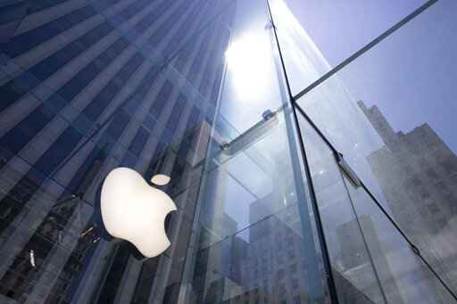 FILE - In this June 16, 2020, file photo, the sun is reflected on Apple's Fifth Avenue store in New York. Apple will cut its app store fee in half from 30% to 15% for most developers beginning Jan. 1, the biggest change in its commission rate since the app store began in 2008. The fee reduction will apply to developers who made up to $1 million from the app store in 2020, which is the