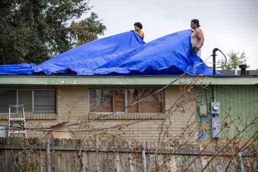 Men cover a roof with tarps, Monday, Sept. 6, 2021, a week after Hurricane Ida swept through the area. (Chris Granger/The Times-Picayune/The New Orleans Advocate via AP)
