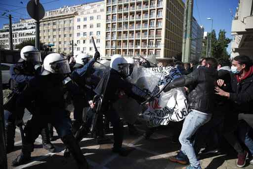 University students clash with riot police during a rally in Athens, Thursday, Jan. 14, 2021. Police have used tear gas to disperse crowds at a rally in the Greek capital organized to protest plans to set up a state security division at university campuses. (AP Photo/Thanassis Stavrakis)